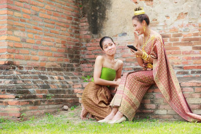 Young beauty with maid dressed in traditional clothes have fun happy shopping in smartphone using modern telecommunication tech stock photo