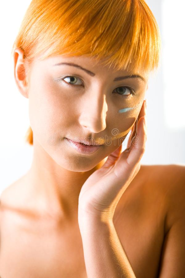 Young beauty putting face cream royalty free stock photography