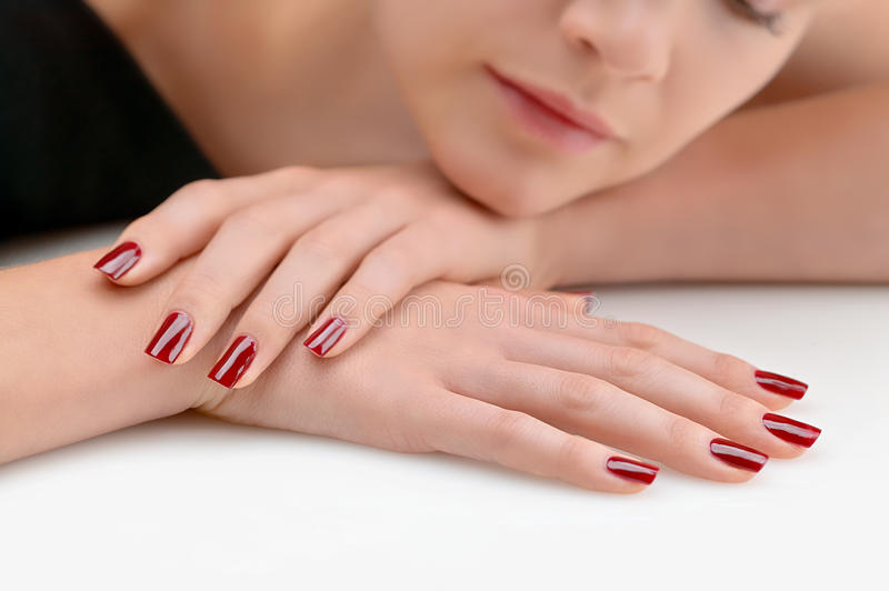 Young beauty with red painted nails. Very relaxed stock photos