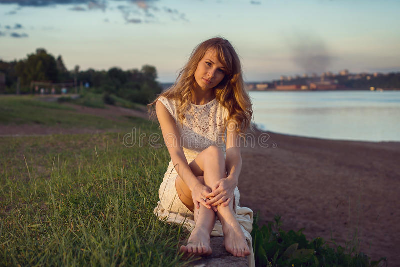 Young beauty smiling relaxing girl woman sitting. Near river or lake in nature outdoors portrait. Soft sunny colors. Sunset sunbeams royalty free stock photo