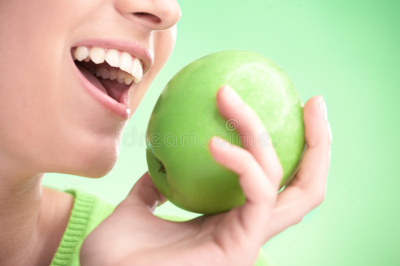 Young beauty woman with apple. On green background royalty free stock photos