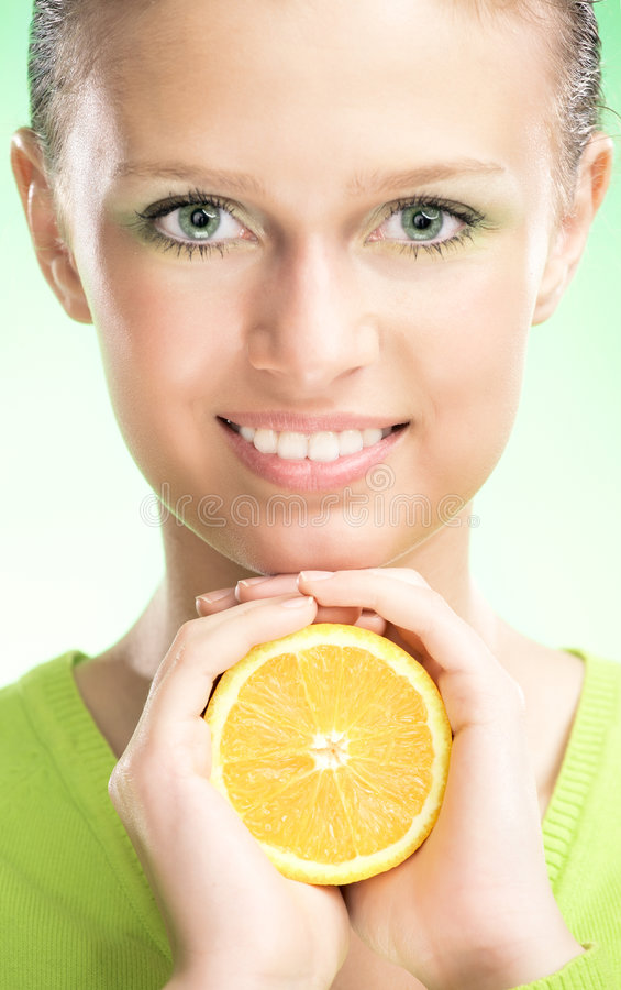 Young beauty woman with apple. Young beauty woman with orange on green background stock image