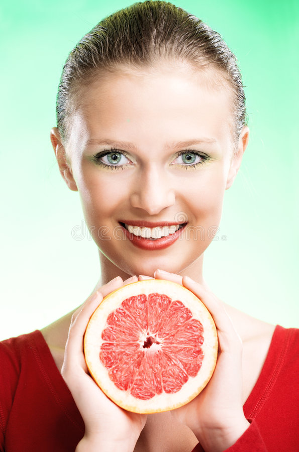 Young beauty woman with apple. Young beauty woman with grapefruit on green background stock image