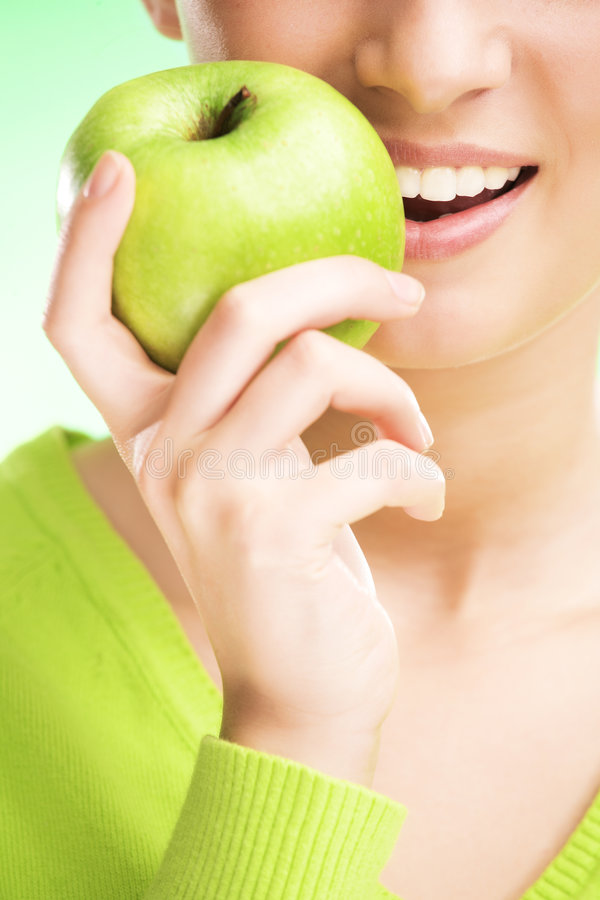 Young beauty woman with apple. On green background stock images