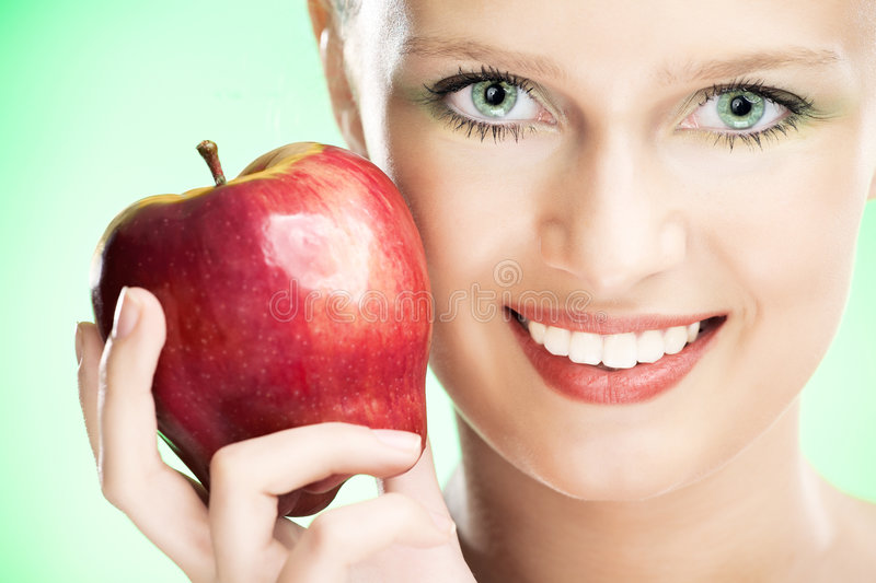 Young beauty woman with apple. On green background royalty free stock image