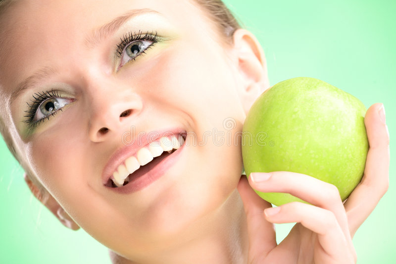Young beauty woman with apple. On green background stock image
