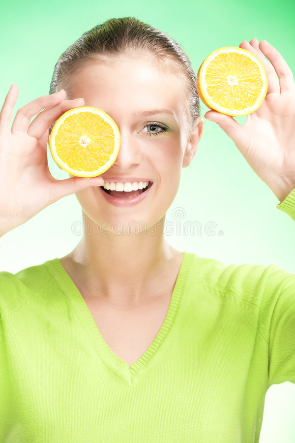 Young beauty woman with apple. Young beauty woman with orange on green background stock photography
