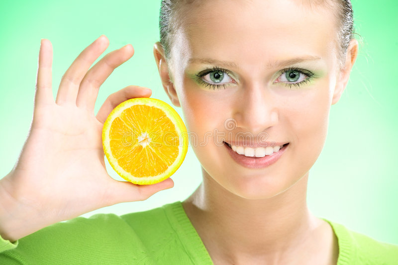 Young beauty woman with apple. Young beauty woman with orange on green background royalty free stock photo