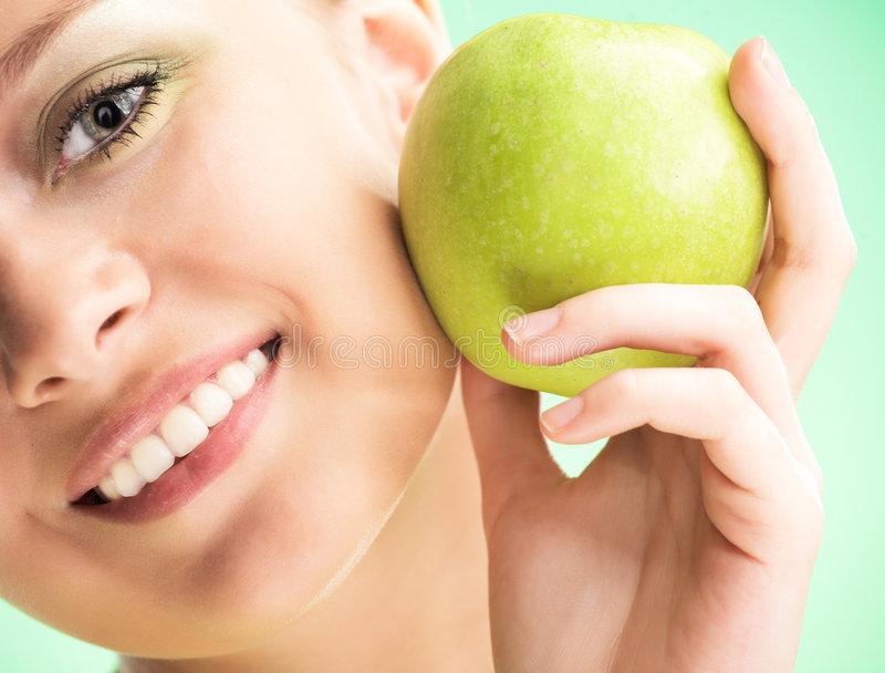 Young beauty woman with apple. On green background stock photos