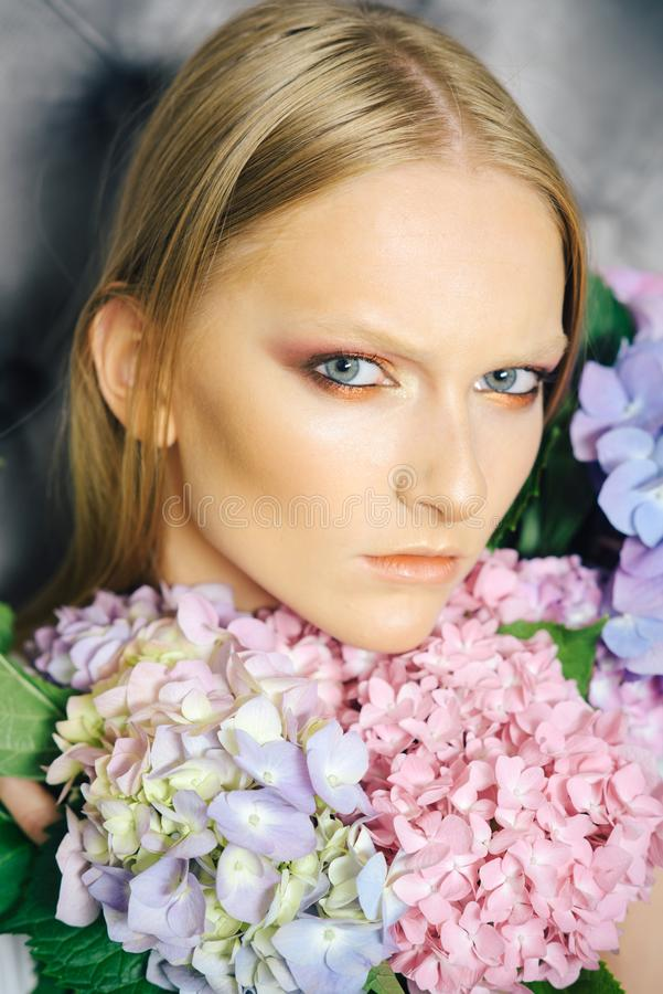 Young beauty woman face with blond hair and hydrangea stock images