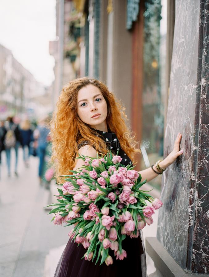 Young beauty woman with flower bouquet. On the spring street. film analog photography royalty free stock photography