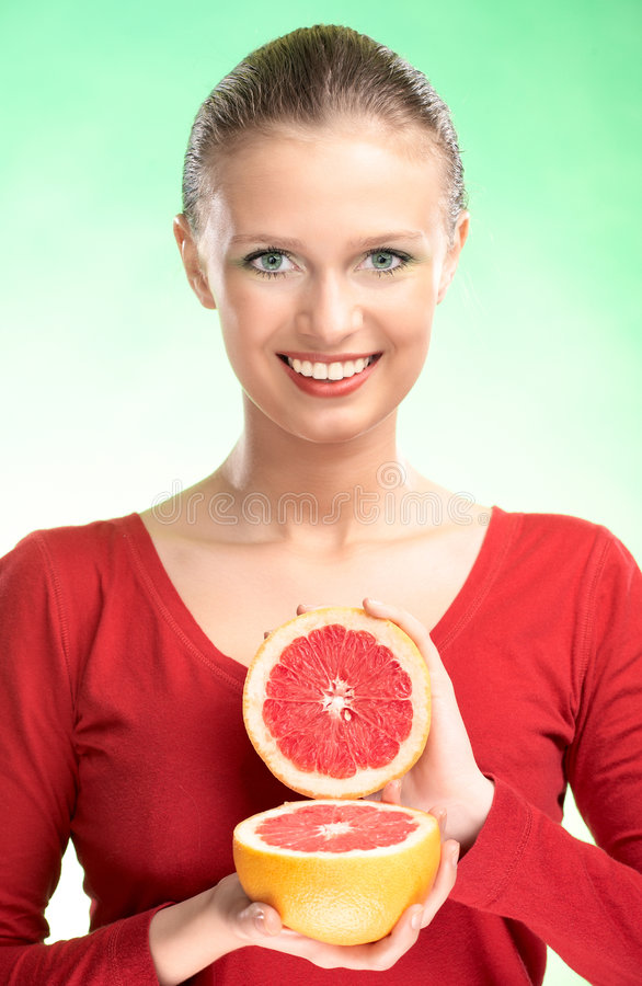 Young beauty woman with grapefruit. On green background stock photos