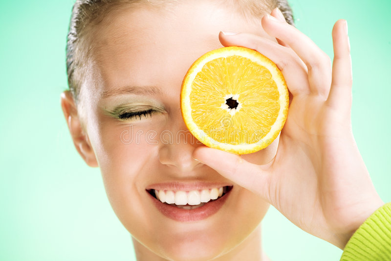 Young beauty woman with orange. On green background stock image