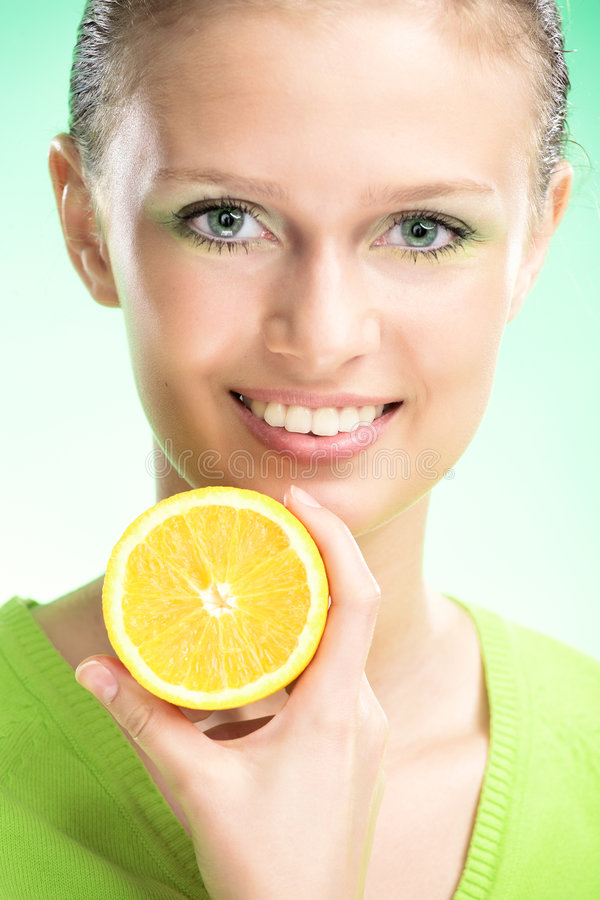 Young beauty woman with orange. On green background royalty free stock photo