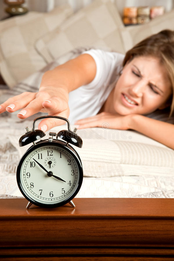 Young beauty woman turning off the alarm clock. Young beauty woman couch in the bed and turning off the alarm clock stock image