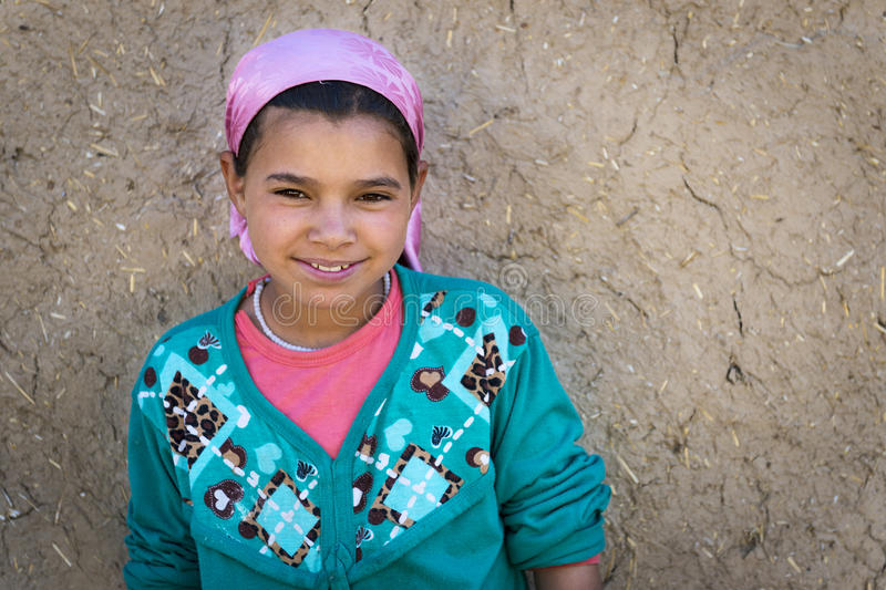 Young Berber girl poses in front of her home in a small Berber village in the Ziz Valley, near Errachidia, Morocco. Errachidia, Morocco - April 12, 2016: Young royalty free stock image
