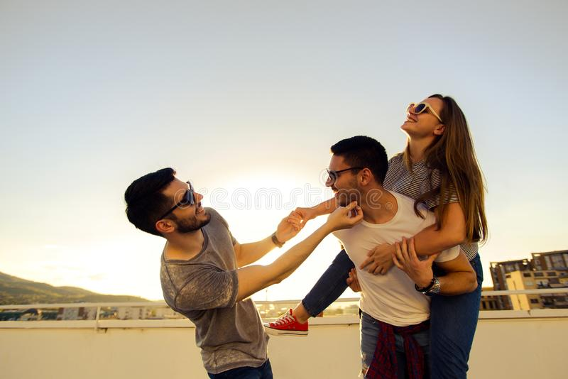 YOUNG BEST FRIENDS CHILLING OUT AND HAVING FUN ON A BUILDING ROOFTOP stock photography
