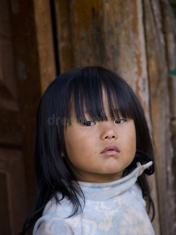 Young Bhutanese girl standing in front of her shed stock photo