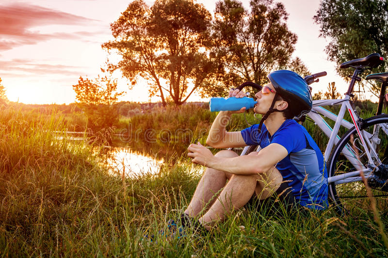 Young bicyclist drinking water by the river royalty free stock photography