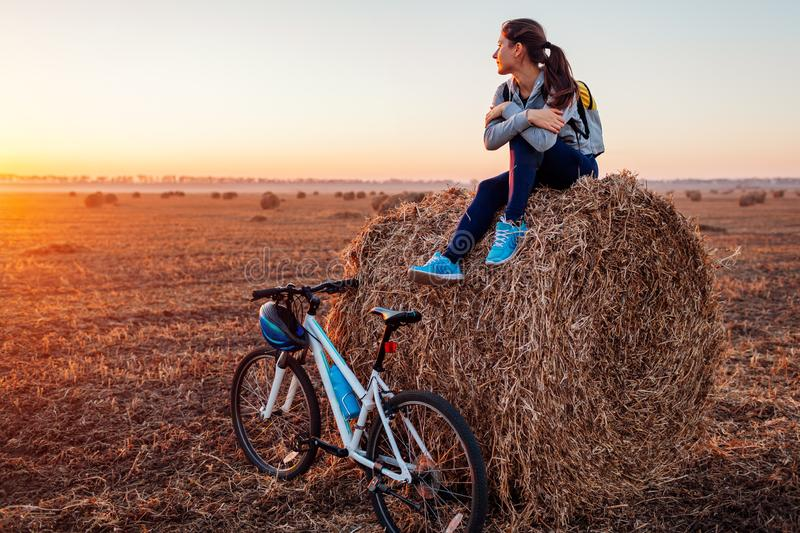 Young bicyclist having rest after a ride in autumn field at sunset. Woman admiring view sitting on haystack. Sport recreation concept stock photo