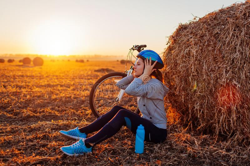 Young bicyclist having rest after a ride in autumn field at sunset. Woman taking off helmet sitting by haystack royalty free stock photography