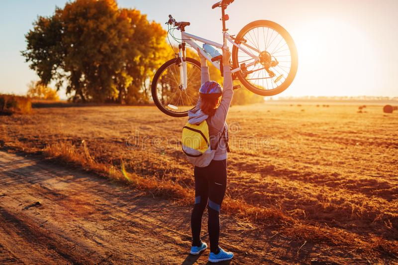 Young bicyclist raising her bicycle in autumn field. Happy woman celebrates victory holding bike in hands. Young bicyclist raising her bicycle in autumn field at stock photography