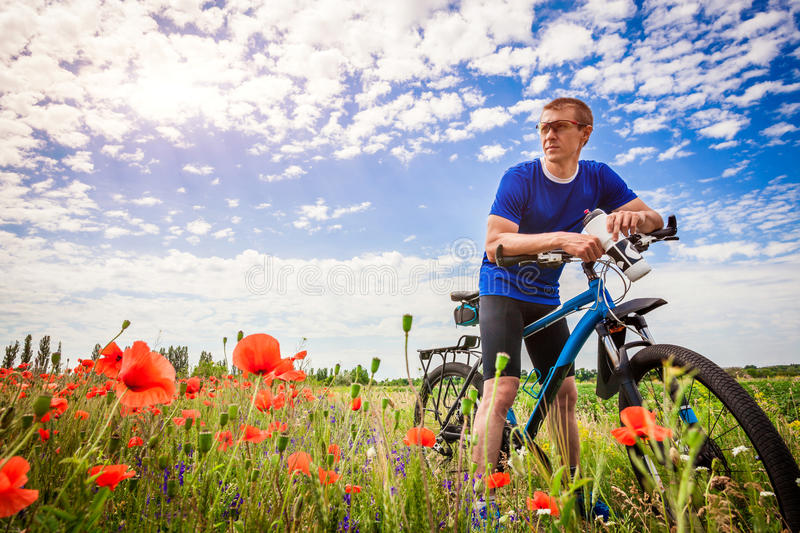 Young bicyclist rides on poppy field stock images