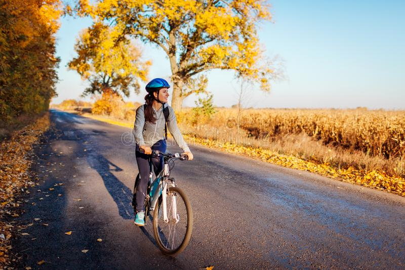 Young bicyclist riding on autumn field road at sunset. Happy woman traveler smiling stock photography