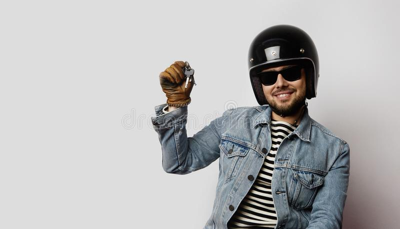 Young biker in a blue denim jacket pretending to ride a motorcycle isolated on white background.Man holding hand moto royalty free stock photos