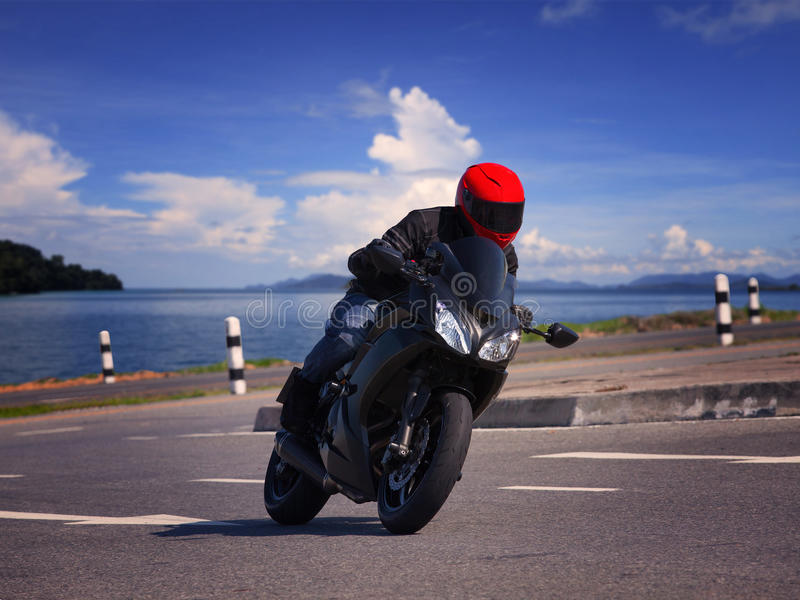 Young biker man riding motorcycle on asphalt road against beautiful sea water background stock photography