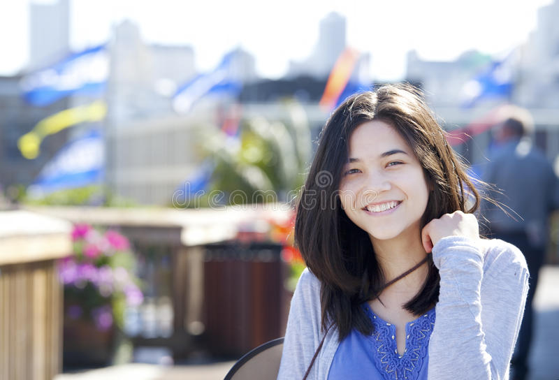 Young biracial teen girl smiling outdoors, sunny background stock photography