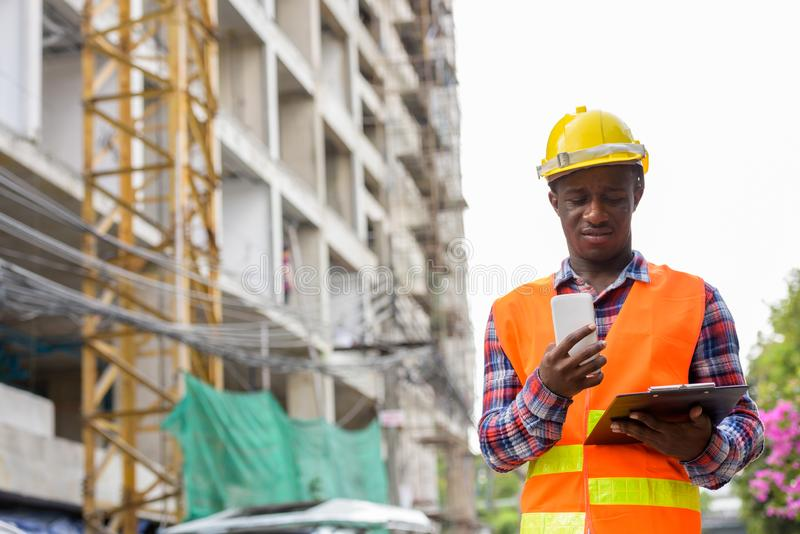 Young black African man construction worker reading on clipboard stock photography