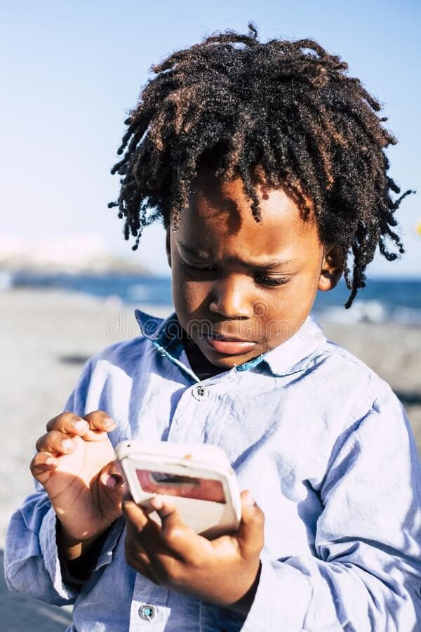 Young black afro children use modern cellular phone with internet games connection - addiction and modern people with technology stock photos