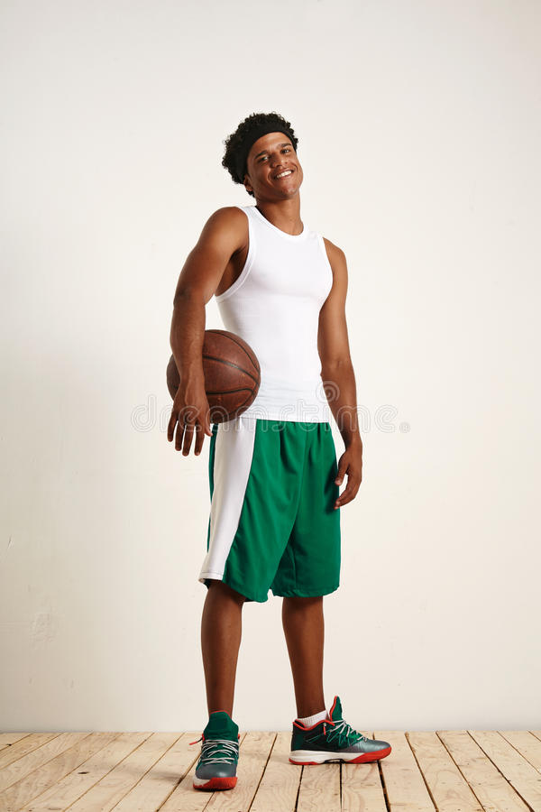 Young black athlete holding a basketball royalty free stock photo