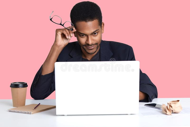 Young black business man with laptop, sits at white table, holds his spectacles in hand, has thoughtful facial expressions, thinks stock images