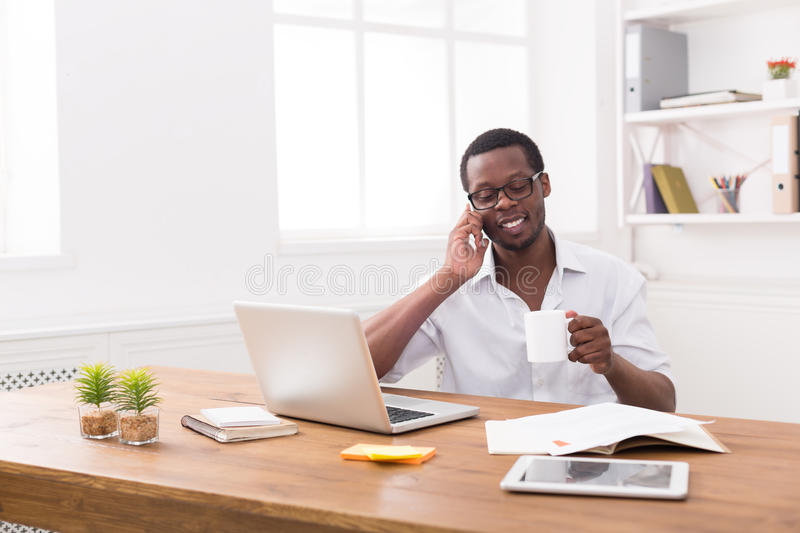 Young black businessman call mobile phone in modern white office stock photos