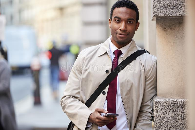 Young black businessman leaning on a wall in the street in London holding phone and smiling to camera, selective focus stock image