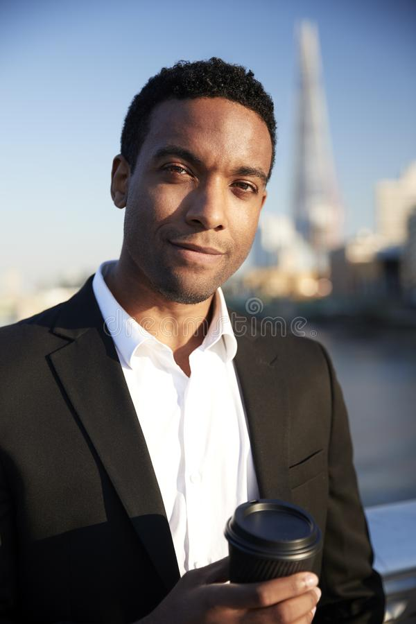 Young black businessman in smart casual clothing standing by the River Thames in London holding a takeaway coffee, looking to came stock photos