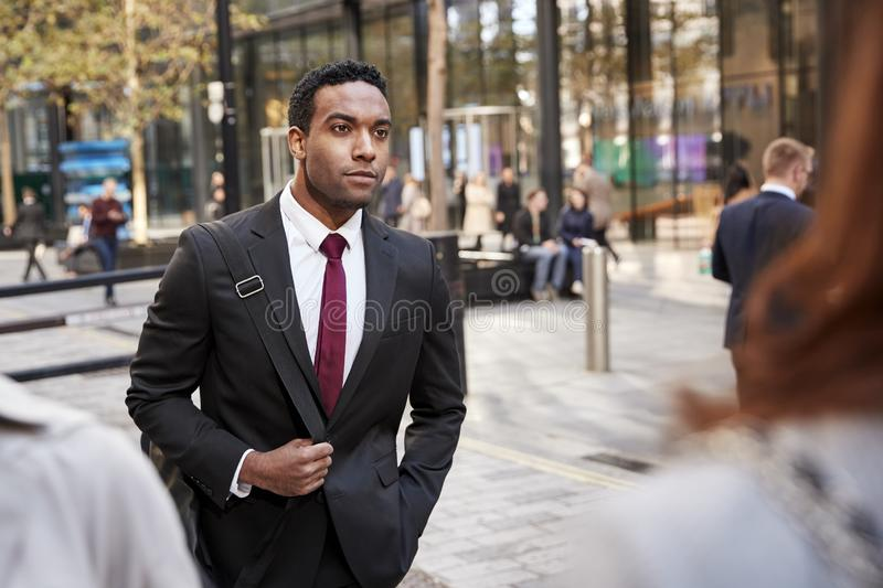 Young black businessman walking in a street in the city, selective focus royalty free stock image