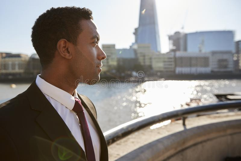 Young black businessman wearing shirt and tie standing by the River Thames, London, looking away, backlit royalty free stock images