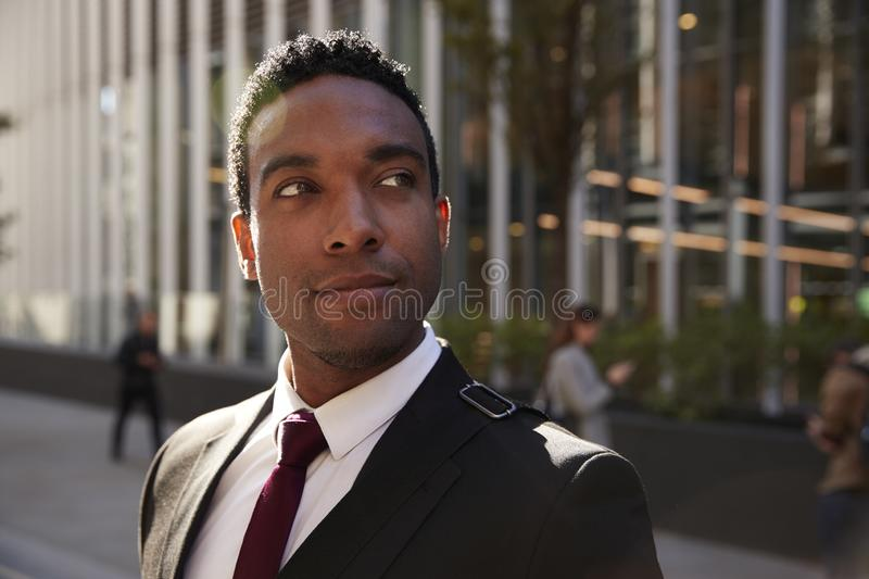 Young black businessman wearing black suit standing on the street smiling, looking away, close up royalty free stock photos