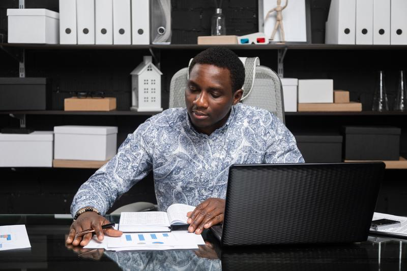 Young black businessman working with documents and laptop in office. Successful successful African top Manager of official shirt works with notebook and laptop royalty free stock photo