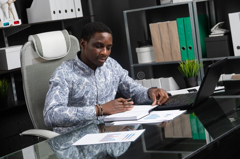 Young black businessman working with documents and laptop in office. Successful successful African top Manager of official shirt works with notebook and laptop royalty free stock photography