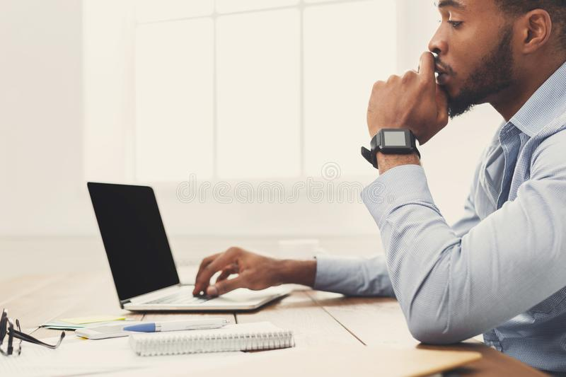 Young black businessman working with laptop stock photography