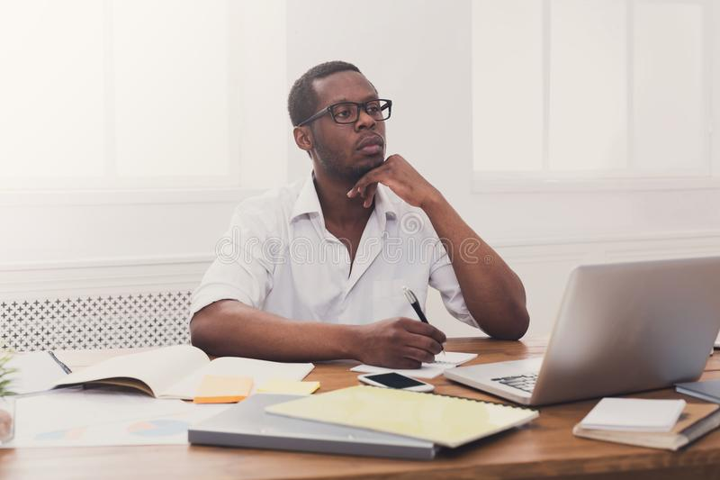 Young black businessman working with laptop in modern white offi royalty free stock image