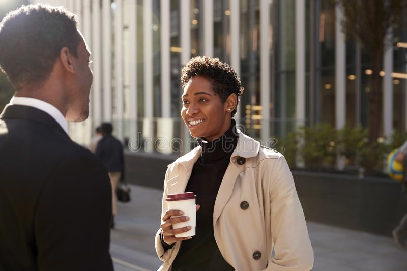 Young black businesswoman standing on the street with a takeaway coffee, talking to her male colleague, selective focus royalty free stock image