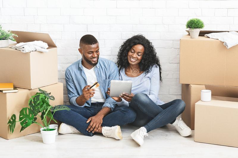 Young black couple buying furniture online, using digital tablet stock photography