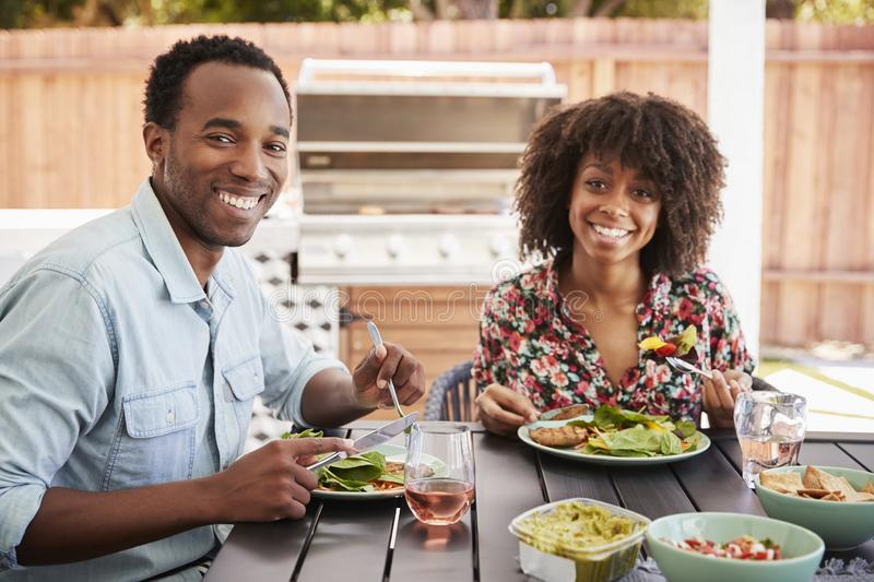 Young black couple eating in the garden looking to camera stock images