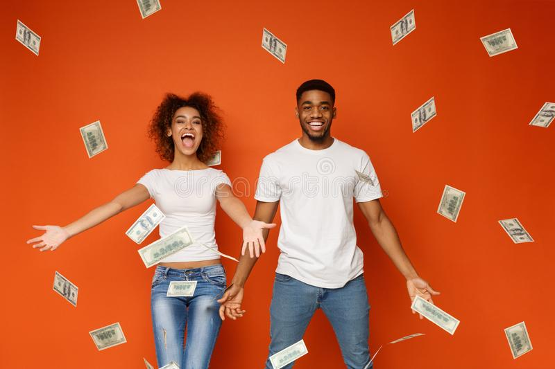 Young black couple enjoying money banknotes shower stock photos