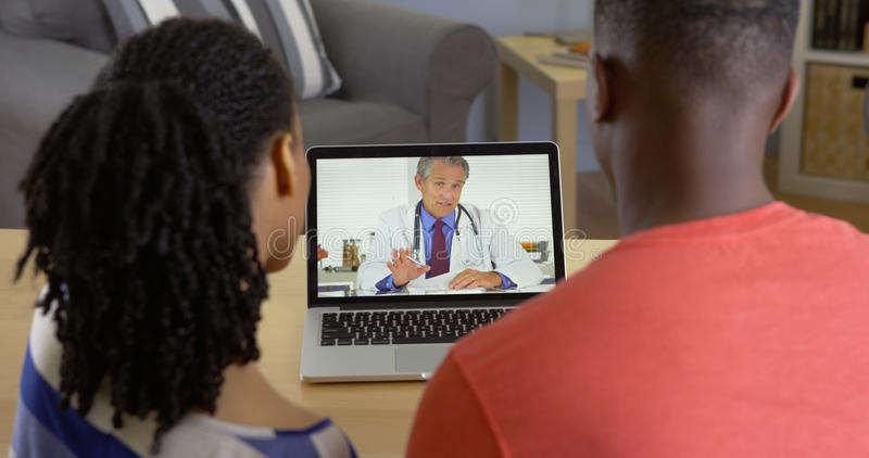 Young black couple having conversation over internet with medical doctor. Serious young black couple having conversation over internet with medical doctor stock photo